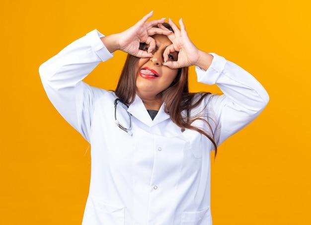 Vrouw arts van middelbare leeftijd in witte jas met stethoscoop die door vingers kijkt en een verrekijker gebaar maakt dat tong uitsteekt