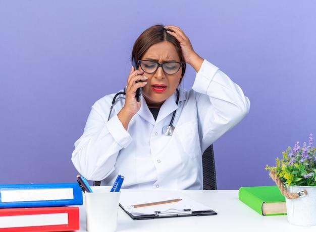 Vrouw arts van middelbare leeftijd in witte jas met stethoscoop die een bril draagt en er verward uitziet terwijl hij op een mobiele telefoon praat terwijl hij aan de tafel zit over de blauwe muur