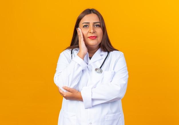 Vrouw arts van middelbare leeftijd in witte jas met stethoscoop die er gelukkig en positief uitziet en glimlacht met de hand op zijn gezicht