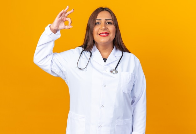 Vrouw arts van middelbare leeftijd in witte jas met stethoscoop die er gelukkig en positief uitziet, zelfverzekerd glimlacht en een goed teken toont