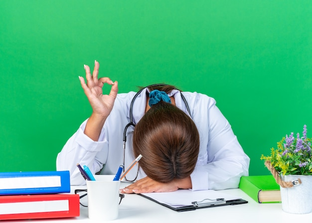 Vrouw arts van middelbare leeftijd in witte jas met stethoscoop die er moe en verveeld uitziet, leunend hoofd op tafel met ok teken met de andere hand zittend aan de tafel op groen