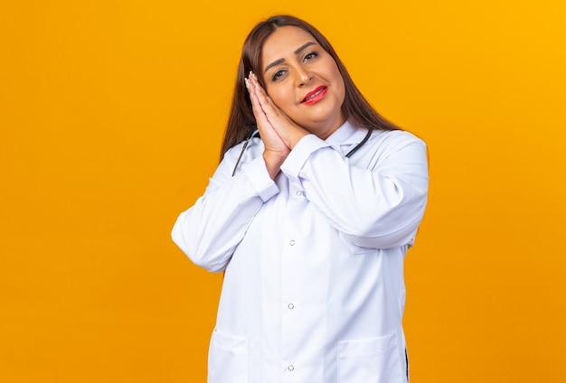 Vrouw arts van middelbare leeftijd in witte jas met stethoscoop die handpalmen bij elkaar houdt en slaapgebaar maakt met het hoofd op de handpalmen