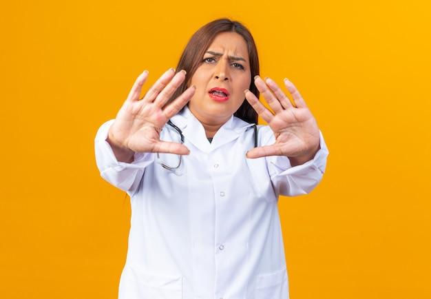 Vrouw arts van middelbare leeftijd in witte jas met stethoscoop die met een serieus gezicht kijkt en een stopgebaar maakt met handen