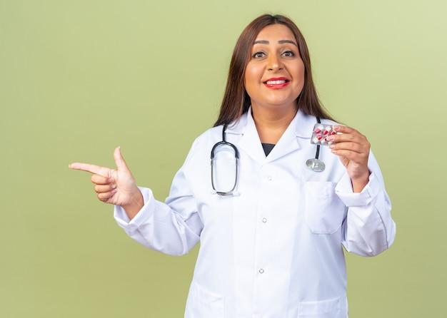 Vrouw arts van middelbare leeftijd in witte jas met stethoscoop met blister met pillen wijzend met wijsvinger naar de zijkant glimlachend zelfverzekerd staande op groen