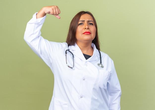 Vrouw arts van middelbare leeftijd in witte jas met stethoscoop met ernstige zelfverzekerde uitdrukking die vuist op groen steekt