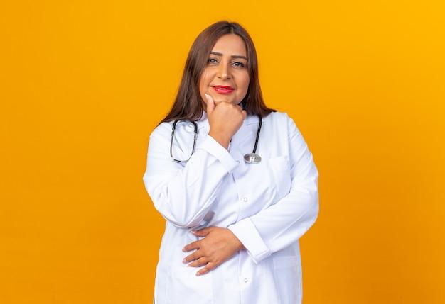 Vrouw arts van middelbare leeftijd in witte jas met stethoscoop met hand op kin glimlachend zelfverzekerd over oranje muur
