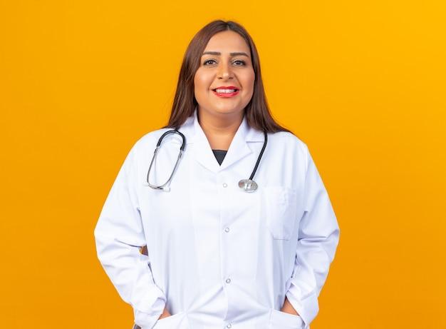 Vrouw arts van middelbare leeftijd in witte jas met stethoscoop op zoek gelukkig en positief glimlachend