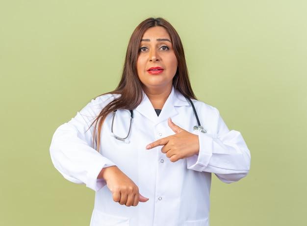Vrouw arts van middelbare leeftijd in witte jas met stethoscoop wijzend met wijsvinger naar haar hand die herinnert aan de tijd die er zelfverzekerd uitziet op groen