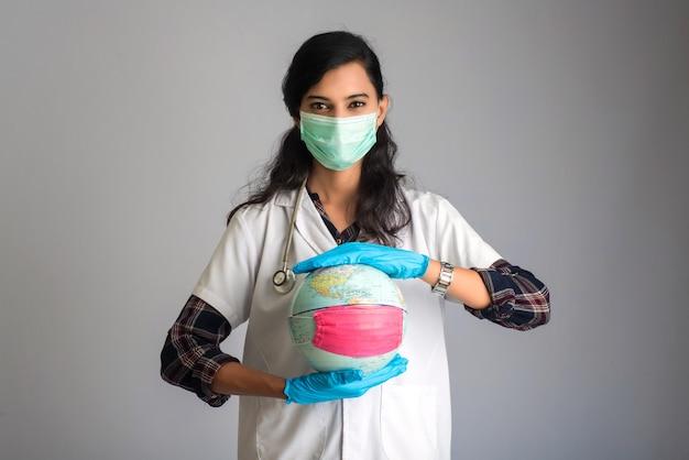 Vrouw arts wereldbol met een geneeskunde gezichtsmasker houden. wereldepidemie van coronavirus concept.