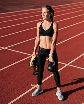Vrouw atleet in sportkleren sportuitrusting in de hand houden op stadion track met rode coating op een zonnige dag