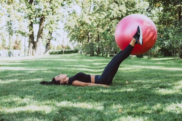 Vrouw atleet met een grote fitness bal traint in het park
