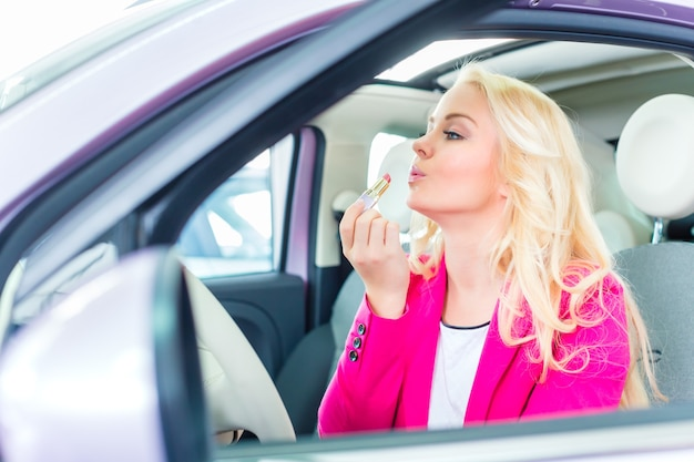 Vrouw auto kopen bij dealer en make-up in spiegel corrigeren