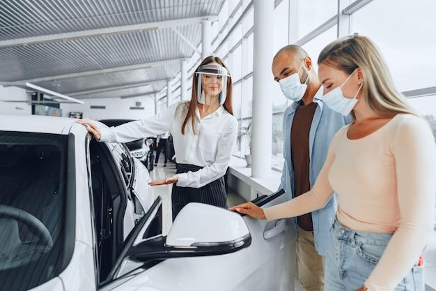 Vrouw autodealer die kopers raadplegen die medisch gezichtsscherm dragen. coronavirus functie-eisen concept