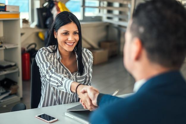 Vrouw autohandelaar handen schudden met client.