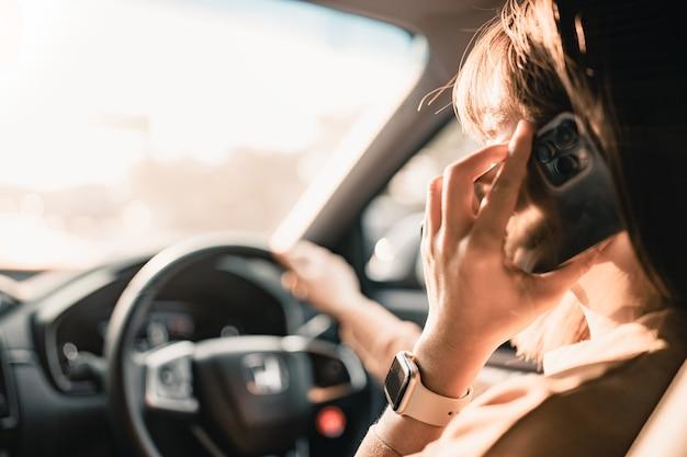 Vrouw autorijden en zakelijke gesprekken voeren met smartphone