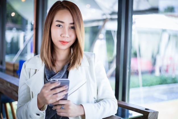 Vrouw aziaat gebruikend telefoon om online te winkelen en roepend met celtelefoon in koffiewinkel tijdens vrije tijd