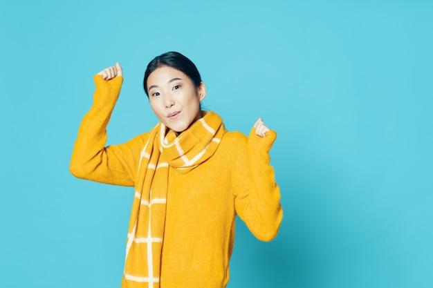 Vrouw aziatisch uiterlijk sjaal gele trui emoties blauwe achtergrond