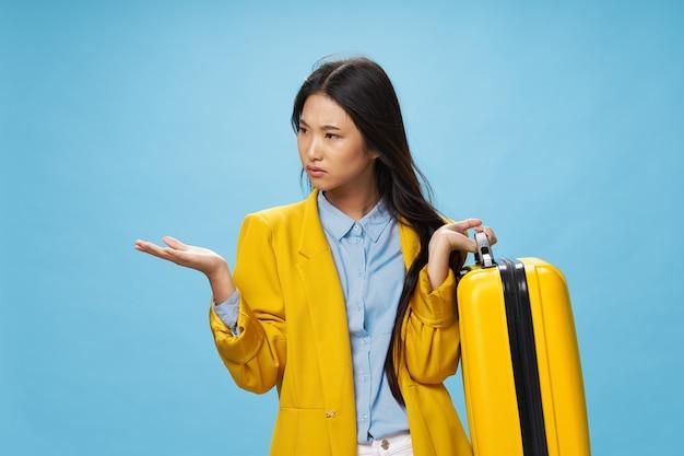Vrouw aziatische reiziger met gele koffer gebaren met handen op blauwe achtergrond. hoge kwaliteit foto