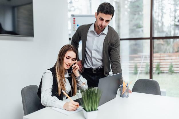 Vrouw baas met haar manager werknemer luisteren online presentatie door laptop.