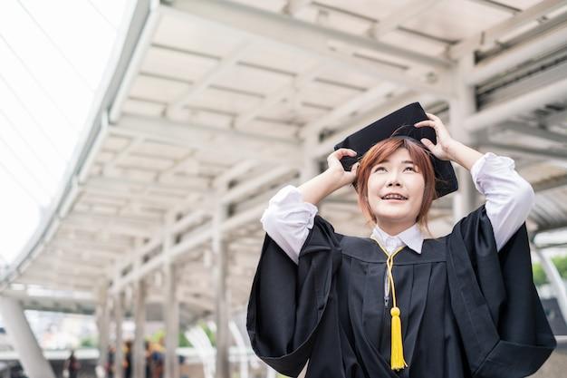 Vrouw bachelor's degree dragen afgestudeerde jurk met hoed te houden