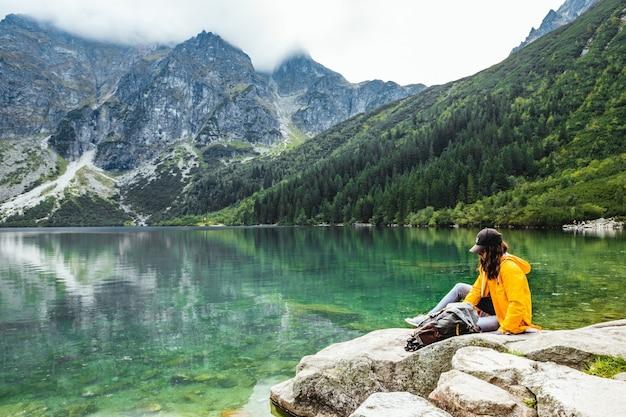 Vrouw backpacker zittend op een rots genietend van het uitzicht op het meer in de bergen van het tatra national park. kopieer ruimte