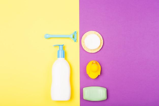 Vrouw bad gezicht lichaamsverzorging ochtend routine bovenaanzicht plat lag samenstelling met witte en blauwe items op geel paars bureau