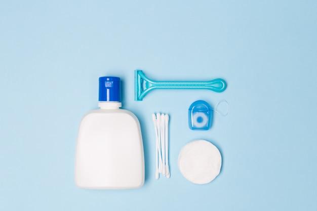Vrouw bad schoonmaak zorg ochtend routine bovenaanzicht plat lag samenstelling met witte en blauwe items op lichtblauw bureau