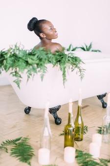 Vrouw badend in een bad vol schuim. mooie afro-amerikaanse bruid in versierd bad