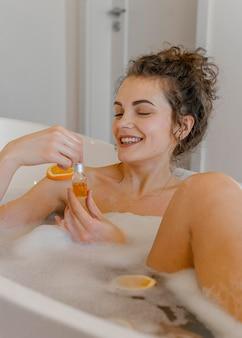 Vrouw badend met stukjes sinaasappel in bad