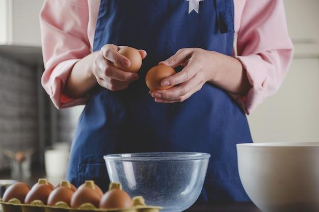 Vrouw bakker in een blauwe schort breekt eieren voor het bakken van huiselijke gezellige kookesthetiek
