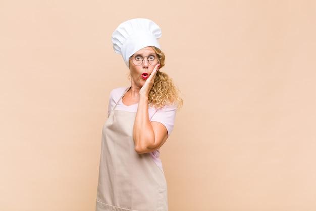 Vrouw bakker van middelbare leeftijd die zich geschokt en verbaasd voelt terwijl ze van aangezicht tot hand in ongeloof met wijd open mond vasthoudt