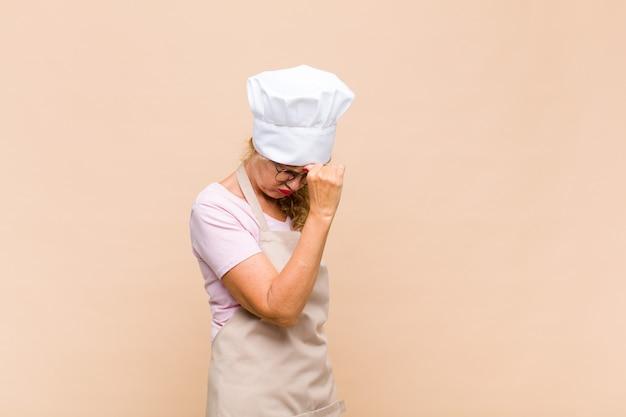 Vrouw bakker van middelbare leeftijd die zich gestrest, ongelukkig en gefrustreerd voelt, het voorhoofd aanraakt en lijdt aan migraine of ernstige hoofdpijn