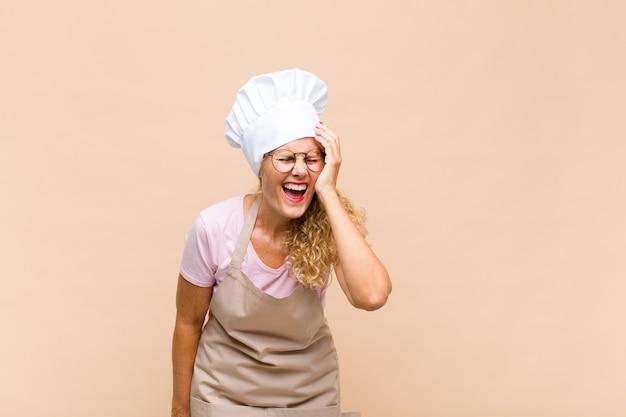 Vrouw bakker van middelbare leeftijd lacht en slaat op het voorhoofd, zoals oh! ik was het vergeten of dat was een domme fout