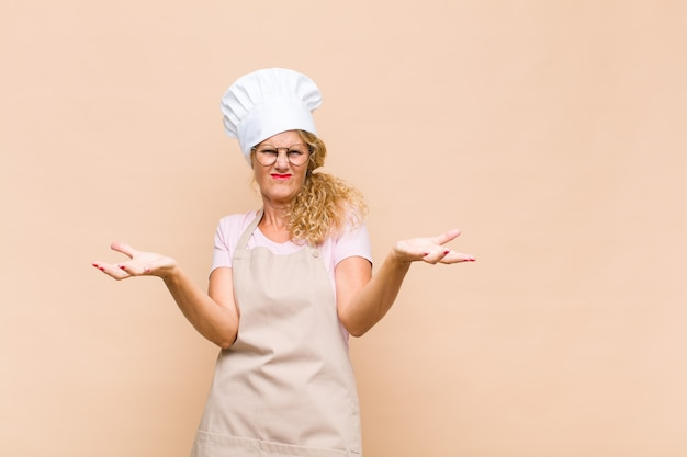 Vrouw bakker van middelbare leeftijd schouderophalend met een domme, gekke, verwarde, verbaasde uitdrukking, geïrriteerd en geen idee