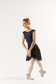 Vrouw ballerina rekt zich uit in de studio