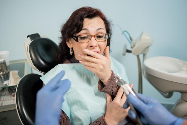 Vrouw bang gemaakt door tandartsen en die haar mond bedekt met de hand op de tandartsafspraak in de tandheelkundige kliniek