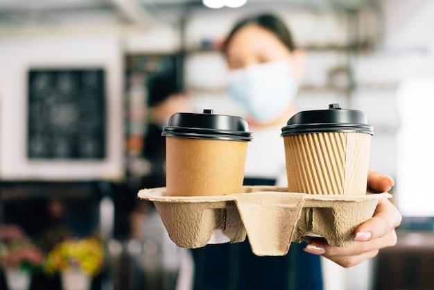 Vrouw barista die een gezichtsmasker draagt en koffie serveert in afhaalmaaltijden papieren wegwerpbekers in de coffeeshop.