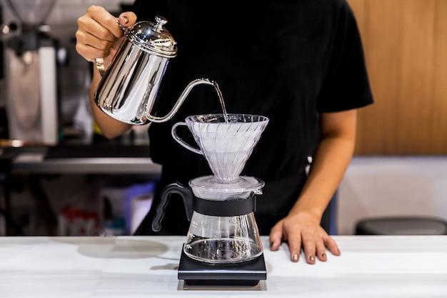 Vrouw barista maken pour-over koffie met alternatieve methode genaamd dripping. koffiemolen, koffiestatief en overgieten op marmeren blad.