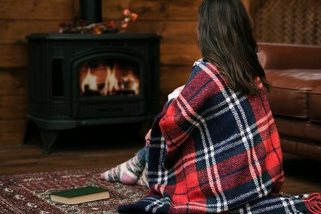 Vrouw bedekt met deken naast open haard