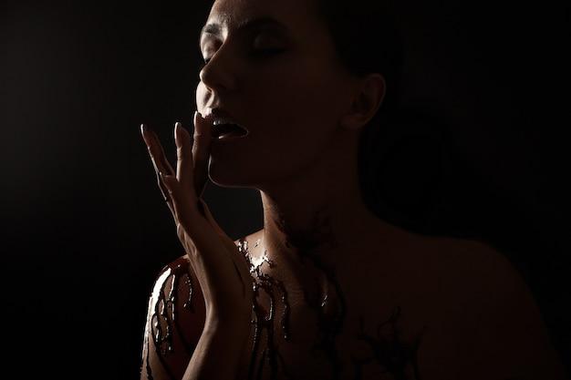 Vrouw bedekt met gesmolten chocolade