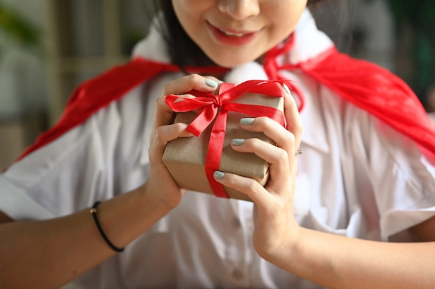 Vrouw bedrijf kerstcadeau met rood lint.