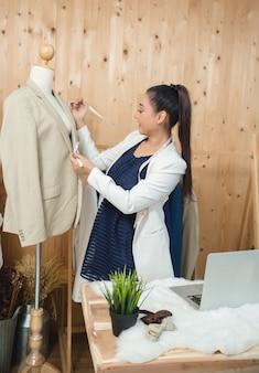 Vrouw bedrijfseigenaar die in haar kleermakerswinkel werkt