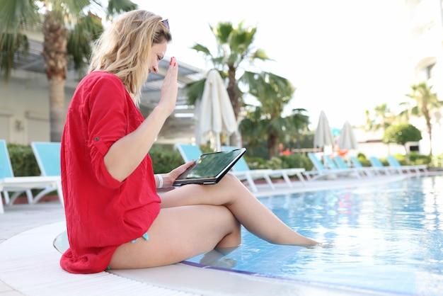 Vrouw begroet gelukkig met hand zakenpartners op tablet terwijl ze in het zwembad zit