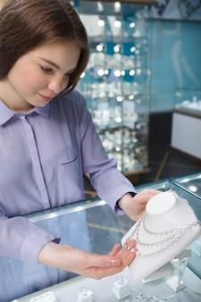 Vrouw behandeling van diamanten halsketting bij juwelier