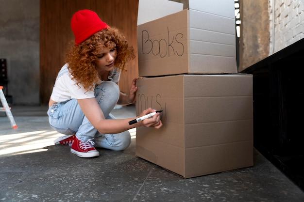 Vrouw behandelt spullen in kartonnen dozen voor verhuizing in nieuw huis