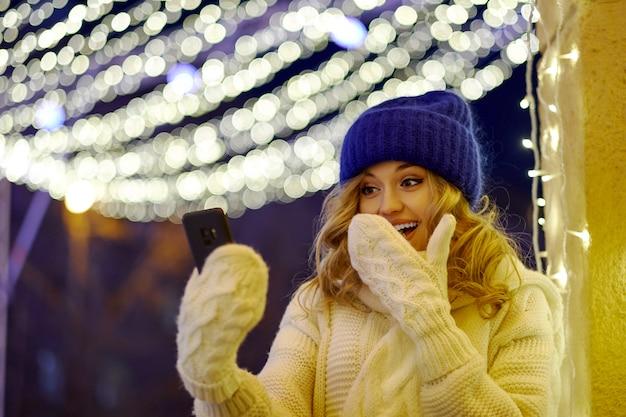 Vrouw bellen feliciteren met kerstmis of nieuwjaar. vrouw met smartphone op feestelijke beurs