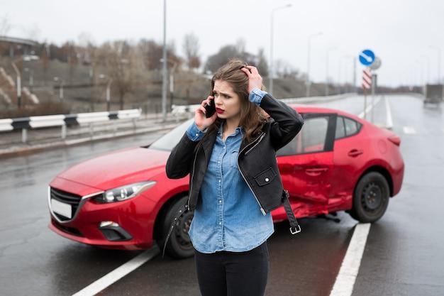 Vrouw belt naar een dienst die bij een rode auto staat
