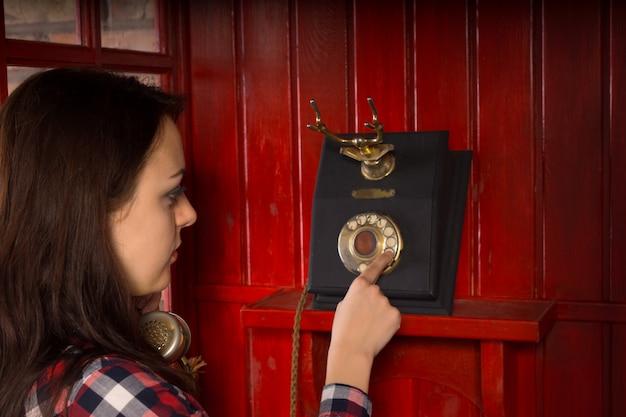 Vrouw belt uit op een vintage telefooninstrument in een houten rode telefooncel
