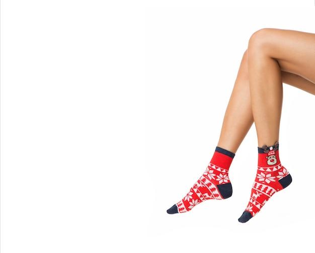 Vrouw benen in kleur rode sokken geïsoleerd op wit benen in kerst sokken