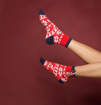 Vrouw benen in kleur rode sokken geïsoleerde benen in kerst sokken